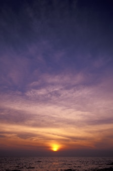Vertical strzał purpurowy i żółty niebo nad morze przy zmierzchem