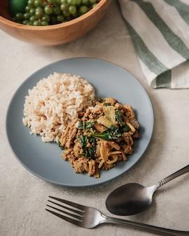 Vertical strzał talerz pełno ryż i kluski blisko rozwidlenia i łyżki na białym stole