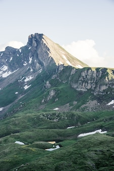 Vertical strzał trawiasty wzgórza blisko góry z jasnym niebem w tle