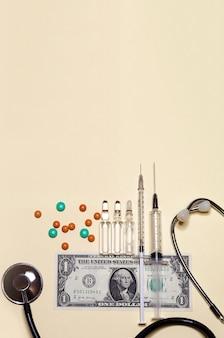 Vertical zaopatrzenie medyczne, stetoskop, strzykawka, ampułka, pastylka na jeden amerykańskim banknocie dolarowym z kopii przestrzenią. koncepcja płatnej medycyny, łapówka w opiece zdrowotnej, wynagrodzenie lekarzy