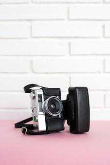 Vintage aparat fotograficzny z lampą błyskową umieszczony na stole przed białym murem w domu