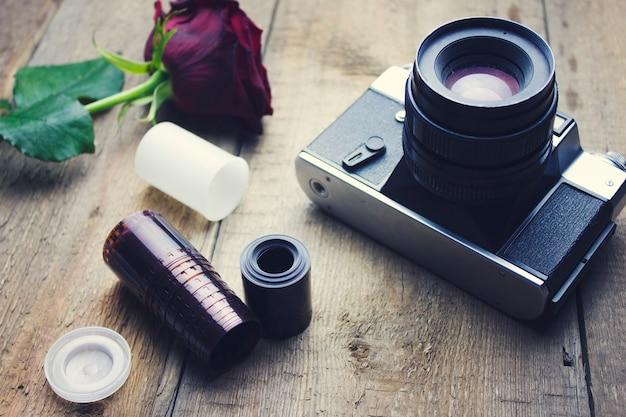 Vintage aparat i róża na drewnianym stole
