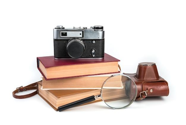 Vintage aparat, książki i lupa na białym tle. widok z boku.