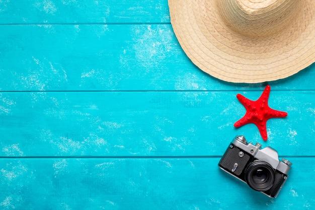Vintage aparat, słomkowy kapelusz i czerwona rozgwiazda na pastelowym niebieskim tle.