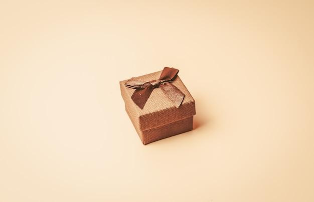 Vintage beżowe pudełko z brązową wstążką na beżowym kolorze