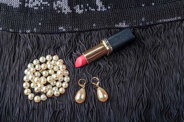 Vintage biżuteria z pereł i czerwona szminka na małej czarnej sukience.