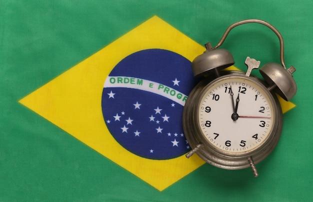 Vintage budzik na tle flagi brazylii
