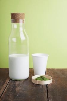 Vintage butelka mleka, biały papier zabiera szkło i organiczną herbatę matcha w proszku premium na brązowym szczotkowanym drewnianym stole przed zielonym prostym tłem