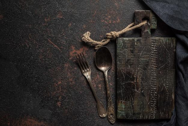 Vintage drewniana deska do krojenia, sztućce i ręcznik kuchenny na ciemnej betonowej powierzchni