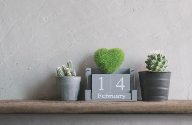 Vintage drewniany kalendarz na 14 lutego z zielonym sercem