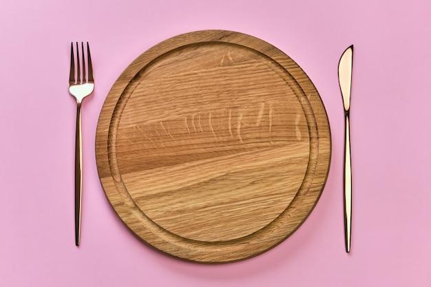 Vintage drewniany talerz i sztućce na różowej powierzchni