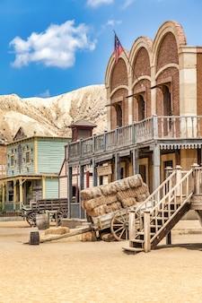Vintage far west miasto z salonem. stara drewniana architektura na dzikim zachodzie na tle błękitnego nieba.