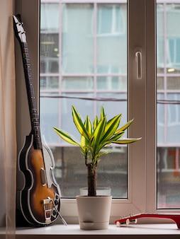 Vintage gitara na konsolę do gier, roślinę i czerwony ukulele na parapecie w deszczowy dzień za oknem