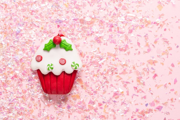 Vintage gliniana babeczka z plasteliny na różowym brokacie. minimalne święta. szczęśliwego nowego roku. leżał z płaskim, widok z góry, miejsce