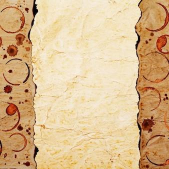 Vintage grunge tekstury spalonego papieru ze śladami filiżanek kawy i plamami kawy na powierzchni