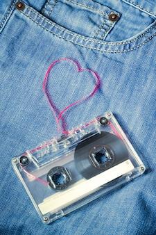 Vintage kaseta audio na niebieskich dżinsach z czerwoną taśmą wyciągniętą w kształcie serca