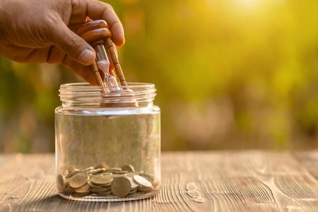 Vintage klepsydra lub klepsydra i monety w słoiku z przezroczystego szkła na drewnianym stole. pojęcie oszczędności czasu i pieniędzy