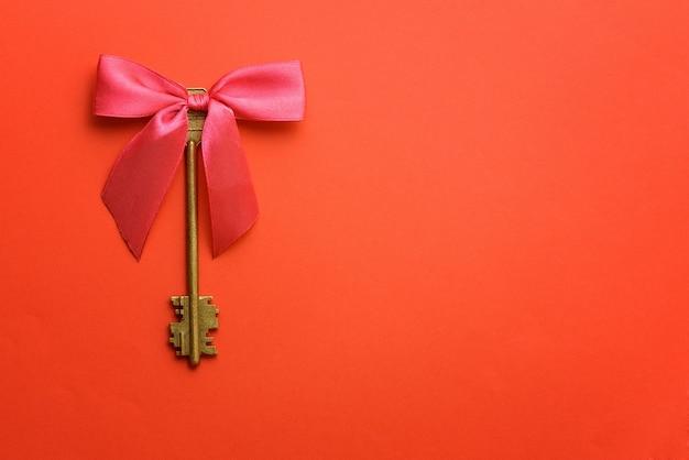 Vintage klucze z różową kokardką na czerwonym tle
