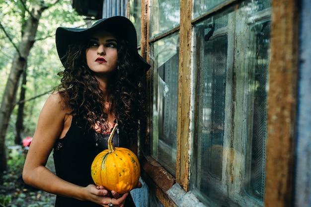 Vintage kobieta jako wiedźma pozuje z dynią w dłoniach na tle opuszczonego miejsca w przeddzień halloween