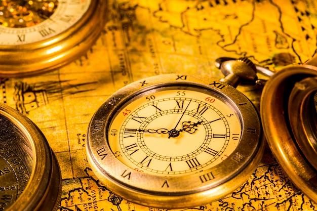 Vintage kompas i zegarek kieszonkowy. mapa świata starożytnego w 1565 r.