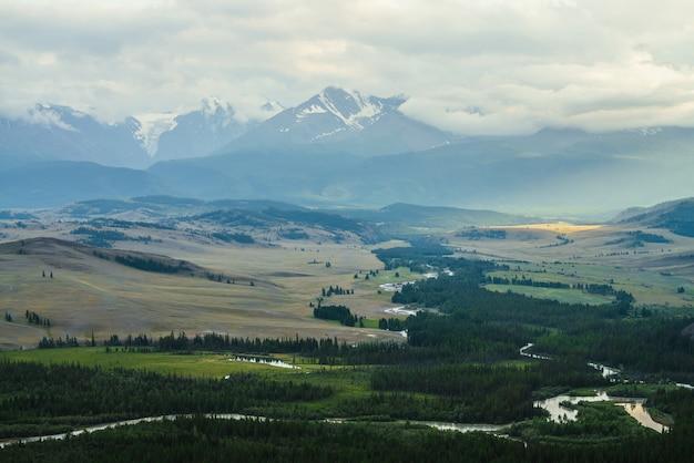 Vintage krajobraz z rozległym płaskowyżem z górską rzeką i lasem na tle ośnieżonego grzbietu górskiego pod zachmurzonym niebem. zielona dolina górska i pasmo górskie śniegu wśród niskich chmur na horyzoncie.