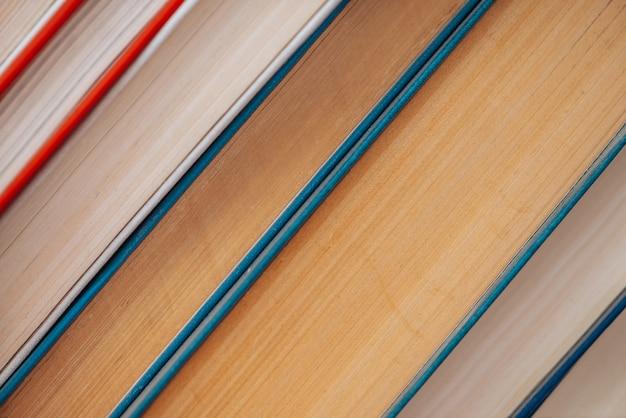 Vintage książki z bliska. stos zużytej starej literatury w szkolnej bibliotece. tło ze starej chaotycznej lektury. zakurzone wyblakłe książki po przekątnej z miejsca kopiowania. stara księgarnia.