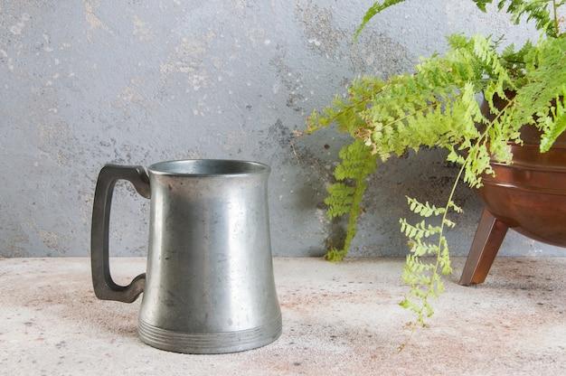 Vintage kubek piwa cyny i zielonych roślin