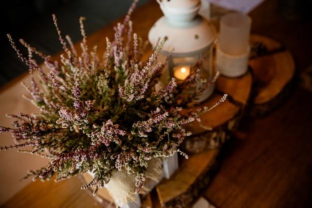 Vintage latarnia z wystrojem świecy i lasu. jesienny styl, kawiarnia, romantyczna dekoracja restauracji. jesienna biała latarnia ozdobiona kolorowymi liśćmi i wieńcem wrzosu.