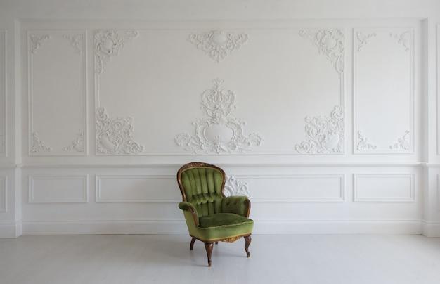 Vintage luksusowy zielony fotel w białym pokoju nad ścianą z płaskorzeźbą sztukaterie listwy rokokowe