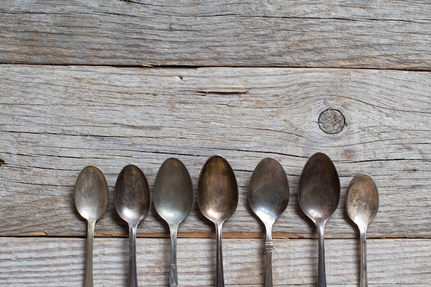 Vintage łyżki z patyną na starym drewnianym stole