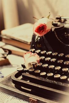 Vintage maszyna do pisania z różową różą, stare książki na stole.