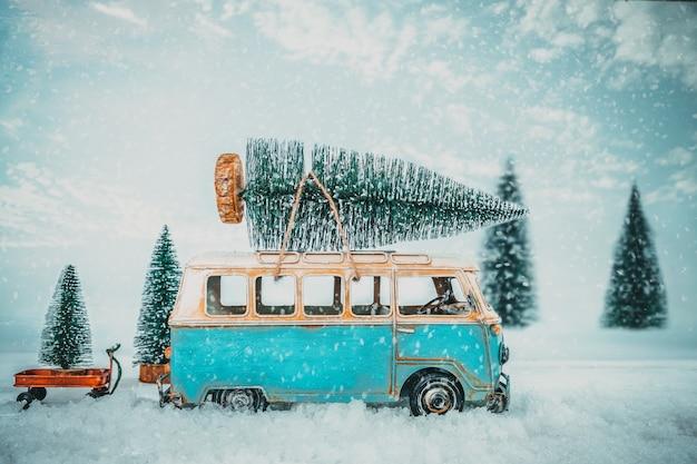 Vintage merry christmas pocztówka tło - miniaturowy zabytkowy samochód przewożący choinkę na dachu w lesie mroźną zimę.
