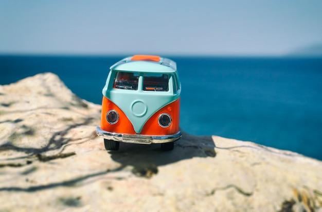 Vintage miniaturowy pomarańczowy i niebieski van. koncepcja podróży