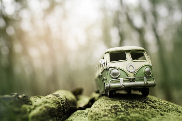Vintage miniaturowy van przejeżdżający przez góry pokryte zielonym mchem. koncepcja podróży i wakacji, płytka głębia ostrości.