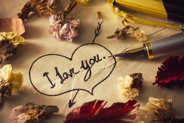 """Vintage mosiężny długopis z napisem """"kocham cię"""" w sercu i strzałka na starym papierze."""