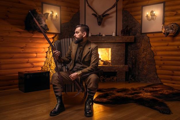 Vintage myśliwy człowiek w tradycyjnej odzieży myśliwskiej siedzi na krześle z karabinem retro przed płonącym kominkiem.