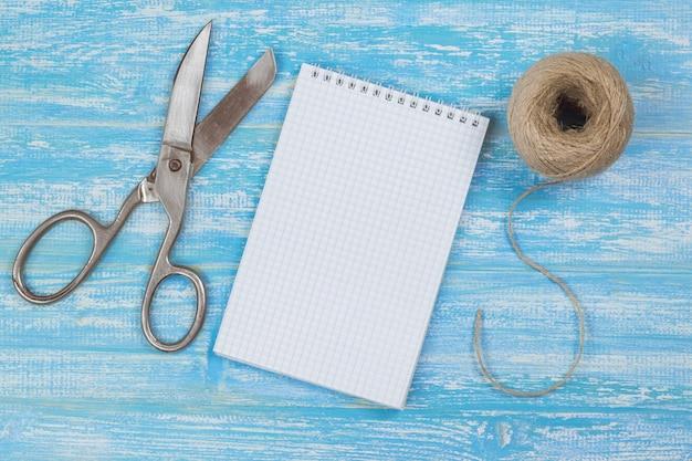 Vintage nożyczki, notatnik i liny na drewnianym stole.