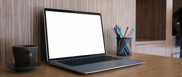 Vintage obszar roboczy z pustym ekranem laptopa, filiżanka kawy, artykuły papiernicze na drewnianym biurku.