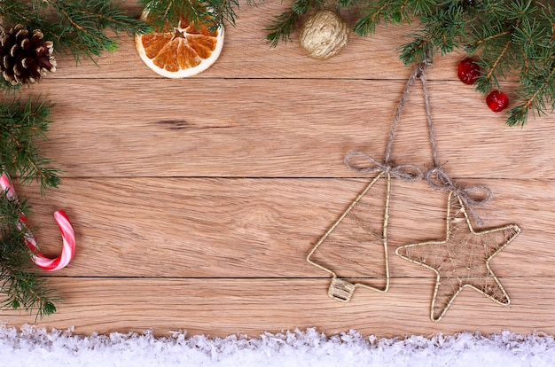 Vintage ozdoby świąteczne na drewnianym tle w otoczeniu gałęzi jodłowych i śniegu