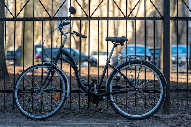 Vintage parken rowerów miejskich przed metalowym ogrodzeniem w słoneczny dzień