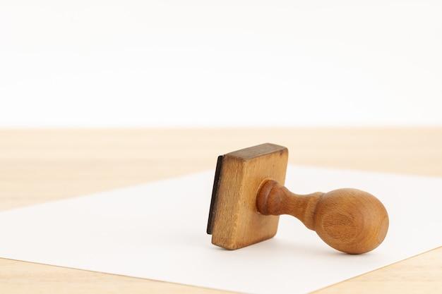 Vintage pieczątka i czysty papier na drewnianym stole. białe tło. skopiuj miejsce