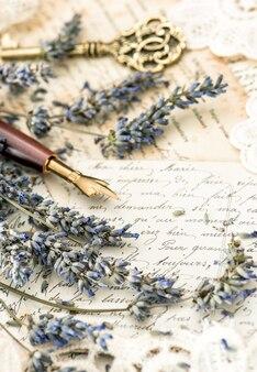 Vintage pióro, klucz, kwiaty lawendy i stare listy miłosne. stonowany obraz w stylu retro!
