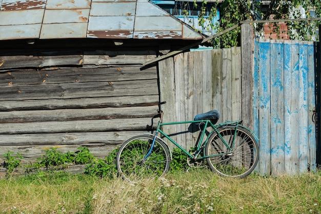 Vintage płotek. stary drewniany płot. tekstura dla projektanta. ogrodzenie we wsi. stary rower