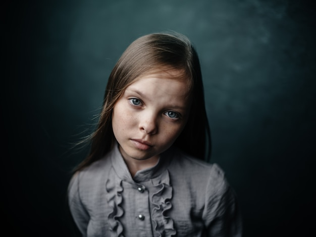 Vintage portret dziewczynki w sukience na ciemnym tle piękna twarz przycięty widok. wysokiej jakości zdjęcie