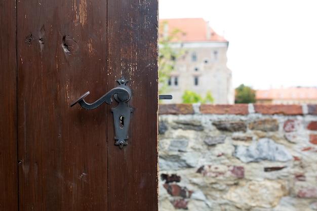 Vintage porysowana klamka brązowych drewnianych drzwi na tle panoramy miasta