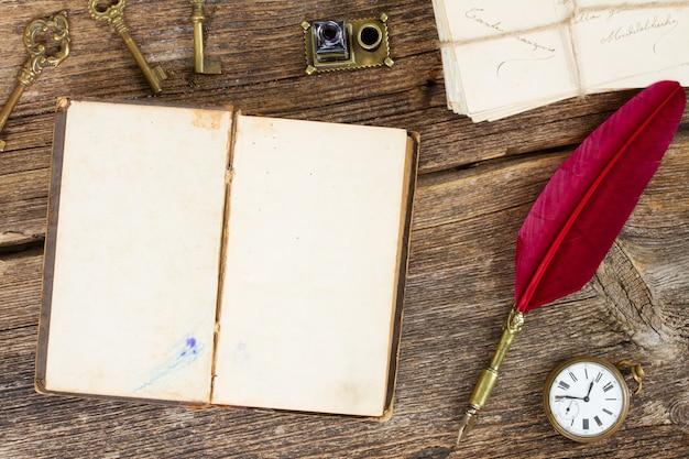 Vintage puste otwarta książka z czerwonym piórkiem i antycznym zegarkiem, widok z góry