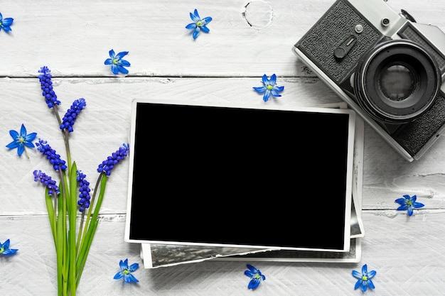 Vintage retro aparat, pusta ramka na zdjęcia i wiosenne niebieskie kwiaty