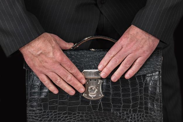 Vintage skórzana teczka w dłoni biznesmena