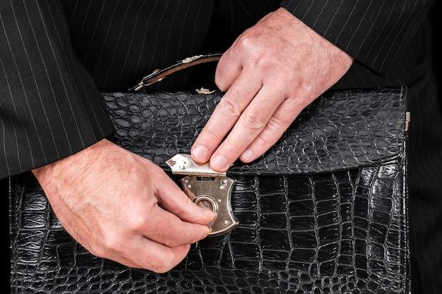 Vintage skórzana teczka w rękach biznesmena, dająca łapówkę