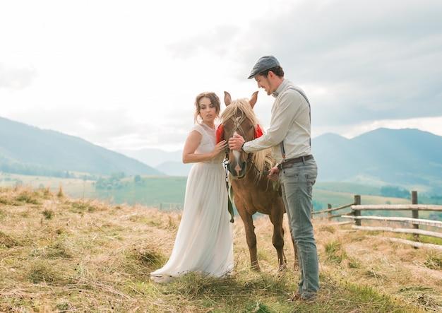 Vintage ślub panny młodej i pana młodego na ranczo z koniem na szczytowych wzgórzach